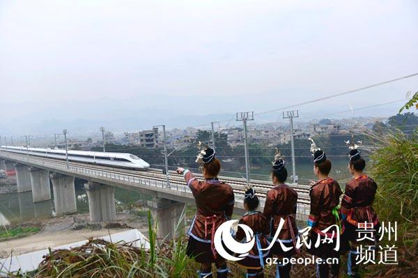 位侗族姑娘在贵广高铁月寨大桥旁观看试运行的动车.-贵州榕江 侗图片