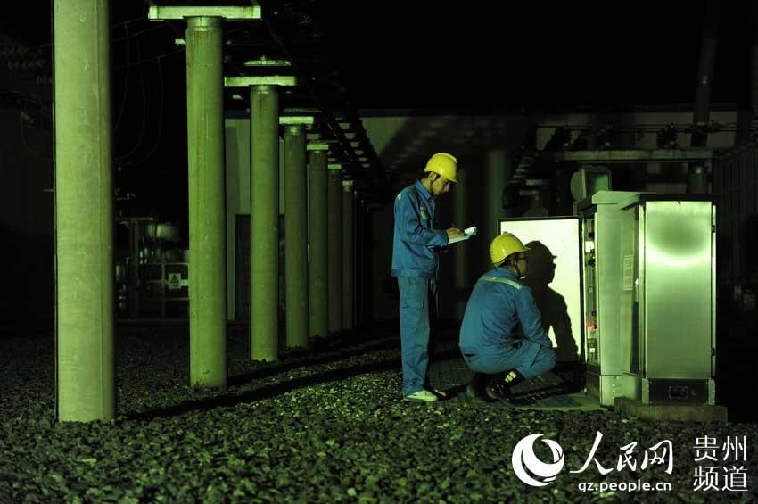 变电站值班人员对电气设备进行检查。