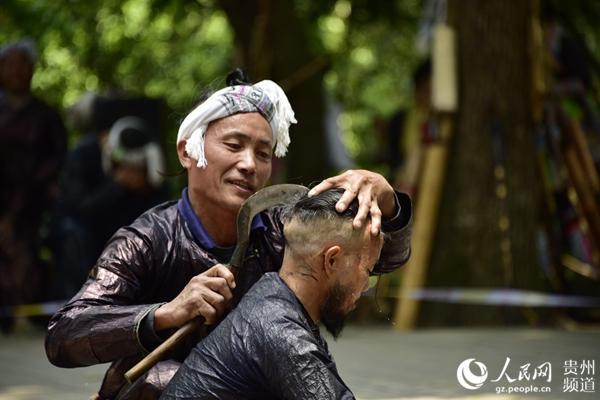 岜沙苗族同胞为游客表演《镰刀剃头》。吴德军 摄