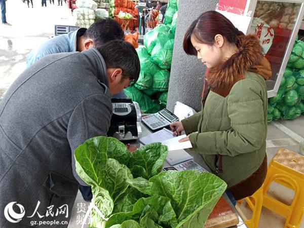 贵州双龙农副产品交易中心蔬菜交易区内,客商进行蔬菜交易。