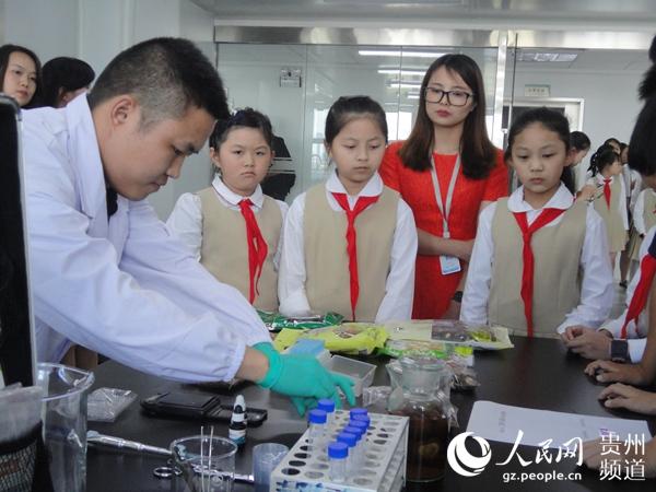 图为:贵州省分析测试研究院食品工程师龙昭航在实验室为小学生讲解食物中二氧化硫的快速检测方法。