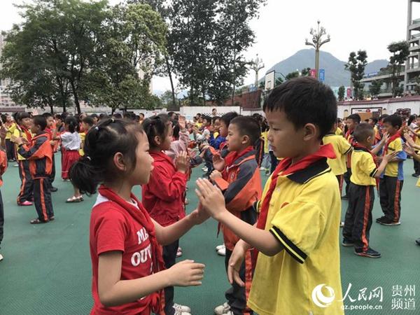 桐梓县娄山关街道鞍山小学操场上,孩子们正在老师的带领下,玩《禁毒拍手歌》游戏。