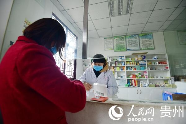 谢厚芝在村卫生室接诊病人。
