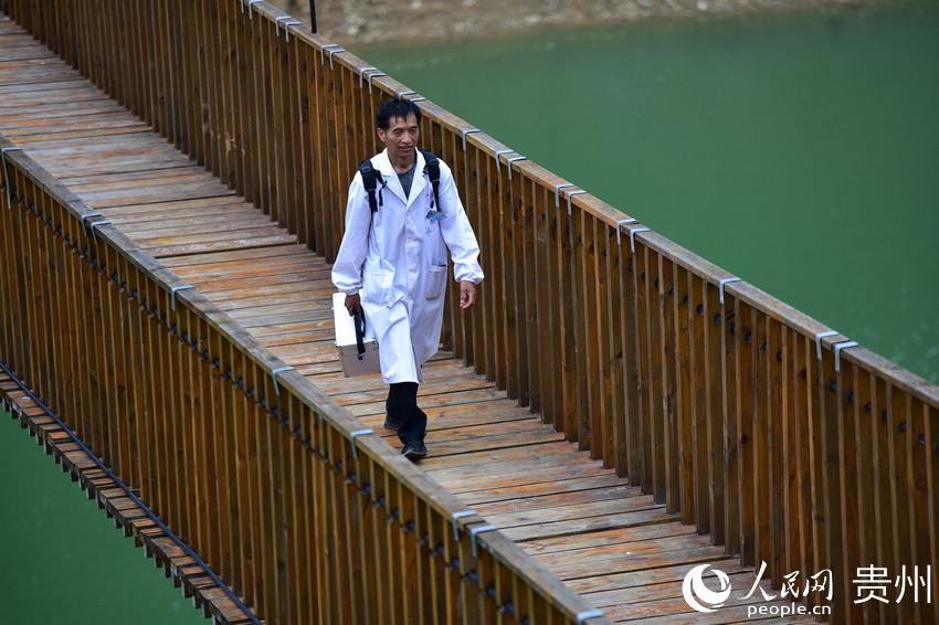 5月27日,出诊返程途中,村医龙光庆行走在贵州省黔东南苗族侗族自治州丹寨县排调镇双尧村的河道铁索桥上。