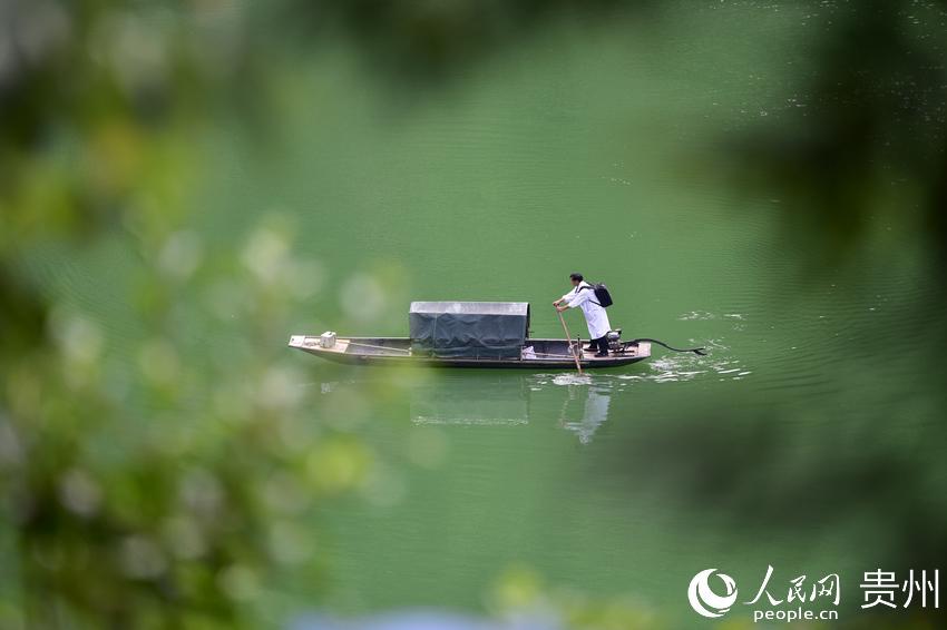 5月27日,出诊途中,村医龙光庆驾驶渡船行驶在贵州省黔东南苗族侗族自治州丹寨县排调镇双尧村的河道上(无人机照片)。