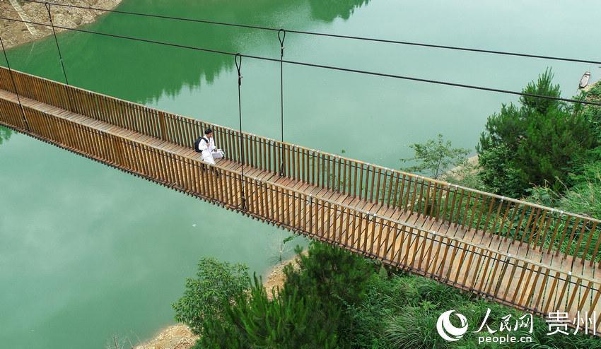 5月27日,出诊返程途中,村医龙光庆行走在贵州省黔东南苗族侗族自治州丹寨县排调镇双尧村的河道铁索桥上(无人机照片)。