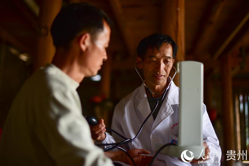 5月27日,村医龙光庆(右)在贵州省黔东南苗族侗族自治州丹寨县排调镇双尧村为村民杨胜良(左)测量血压。